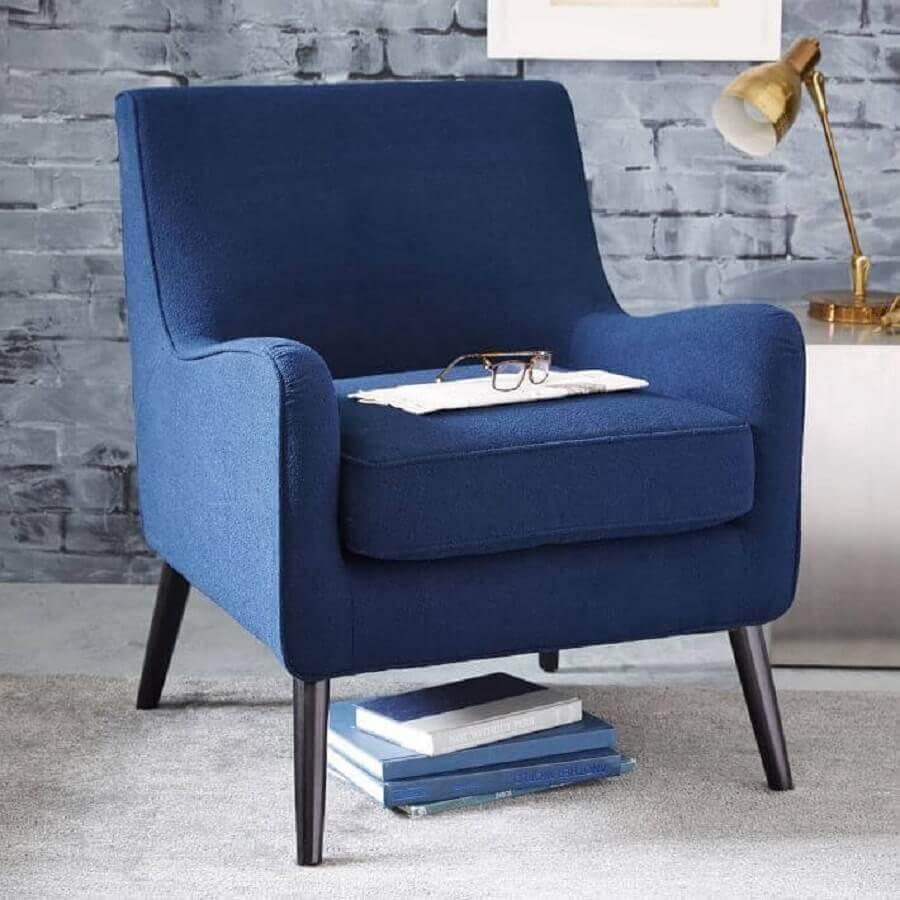 Poltrona azul royal com papel de parede de tijolinhos Foto Mherger