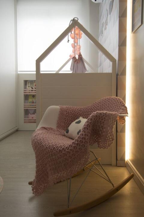 Quarto de bebê com manta em tons de rosa em cadeira de balanço Projeto de Debora Marquardt