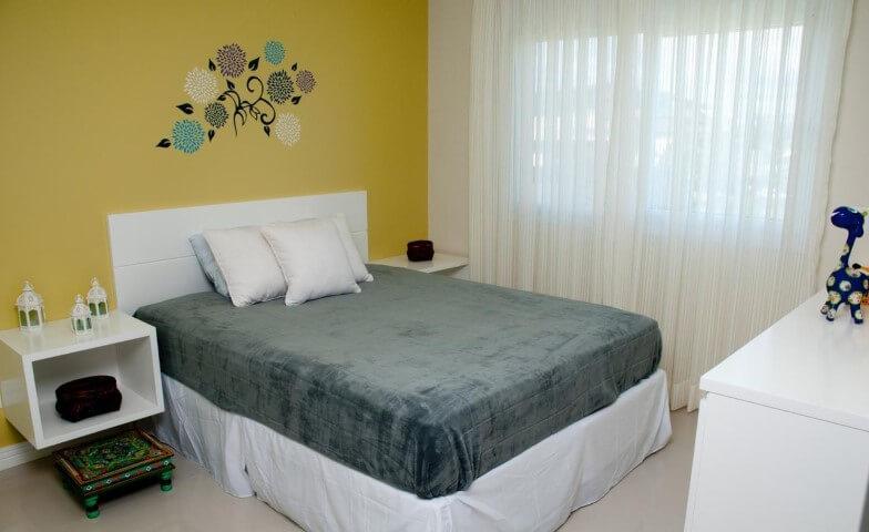 Quarto de casal com parede amarela e cama box com saia branca Projeto de Juliana Pippi
