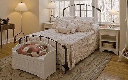 Quarto de solteiro com cama de ferro e calçadeira branca