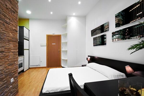 Quitinete com parede de tijolos separando quarto da sala