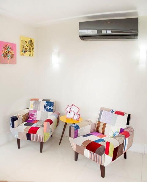 Sala de estar com poltronas de patchwork Projeto de Battaglia Arquitetura
