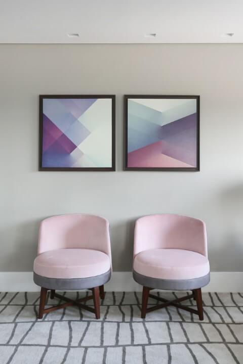 Sala de estar com quadros e poltronas em tons de rosa, cinza e roxo Projeto de Karen Pisaca