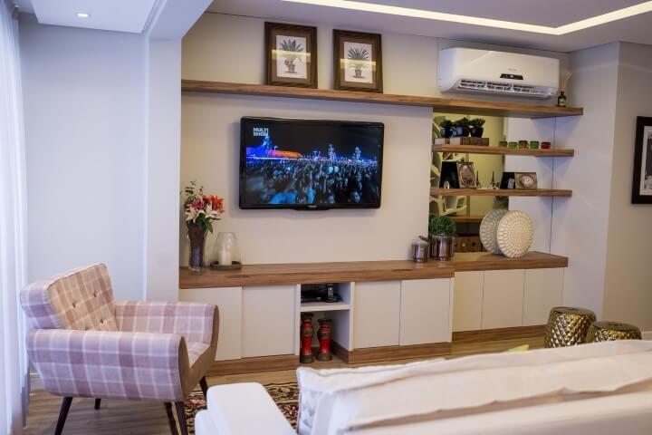 Sala de estar em cores claras e poltrona em tons de rosa Projeto e Inova Arquitetura