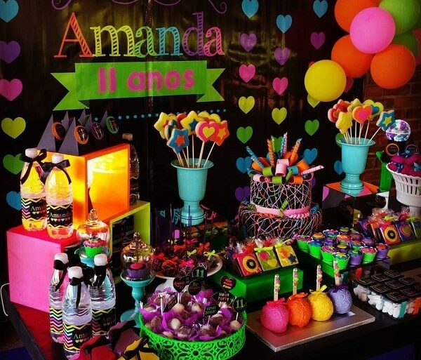 Espalhe doces coloridos pela mesa do bolo da festa neon