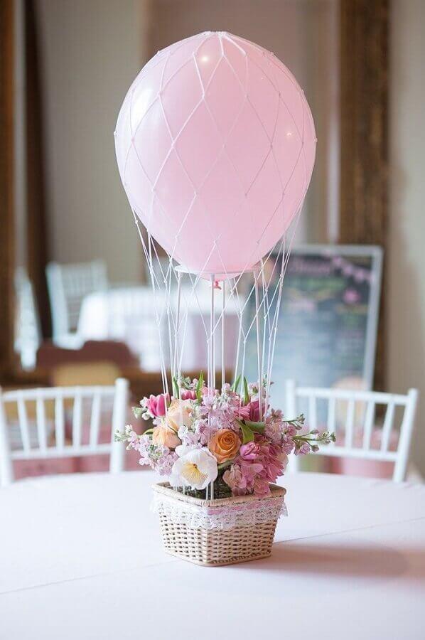 arranjo com flores e bexiga para mesa de convidados em festa de 15 anos