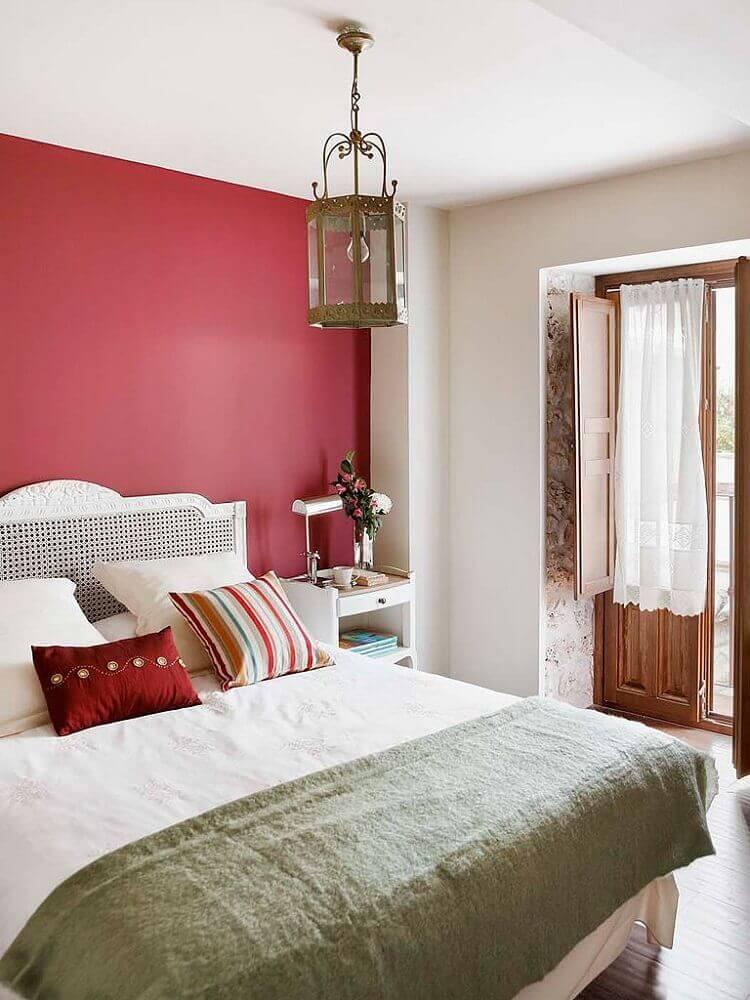 Quarto de casal com parede vermelha e cabeceira de madeira pintada de branco