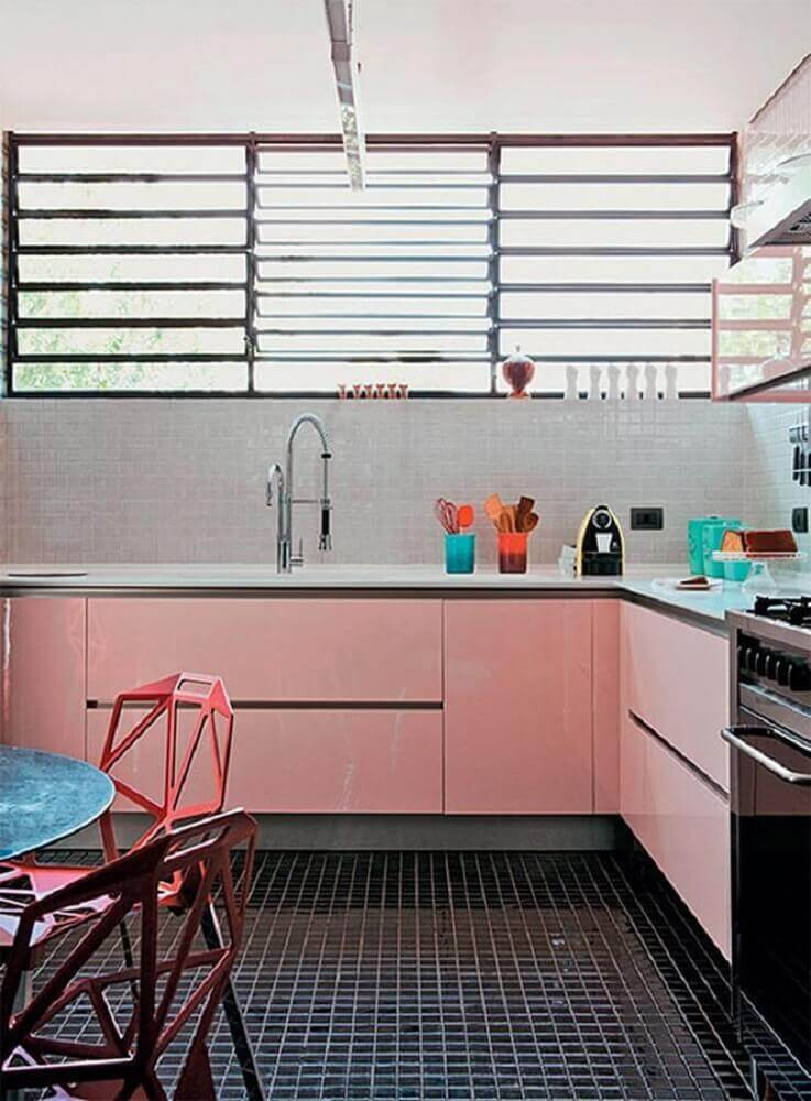 cozinha retrô decorada com armário rosa e piso preto