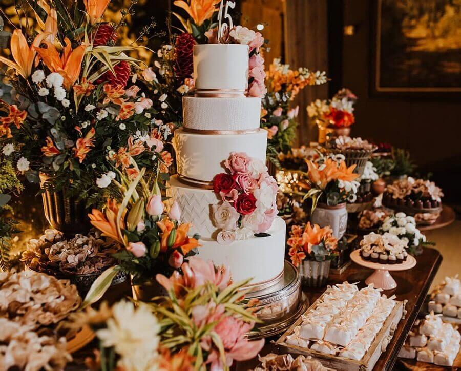 decoração clássica e sofisticada para festa de 15 anos com muitos flores e bolo 5 andares