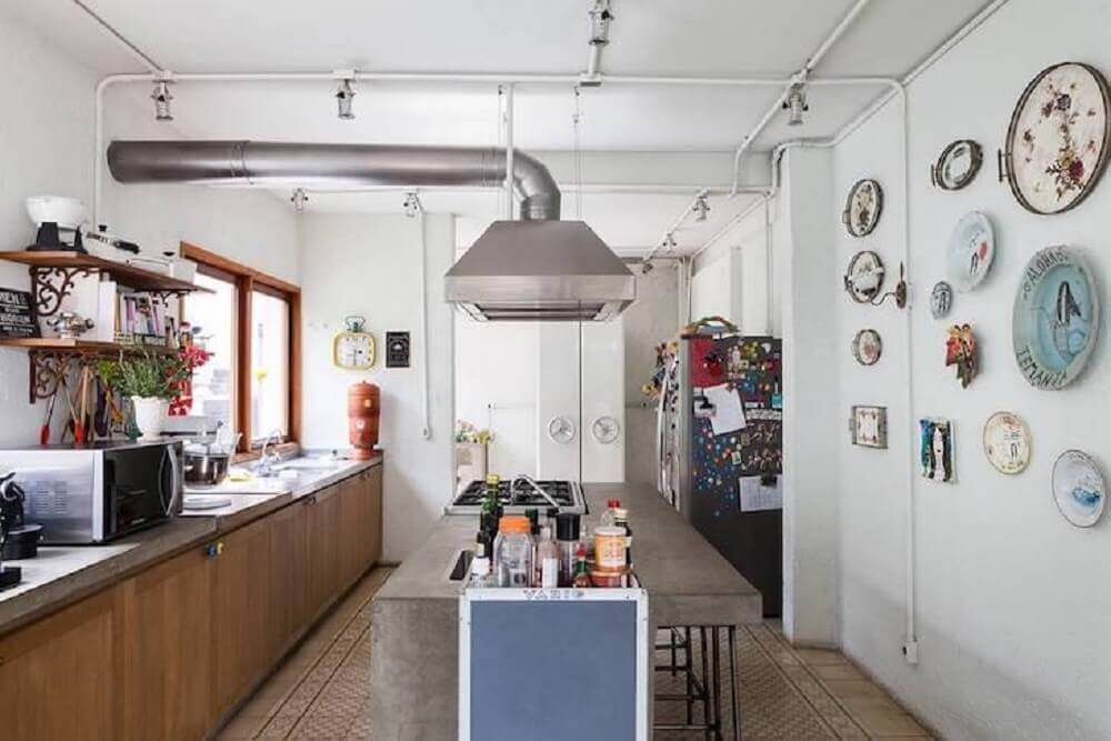 decoração com quadros retrô para cozinha ampla com armários de madeira