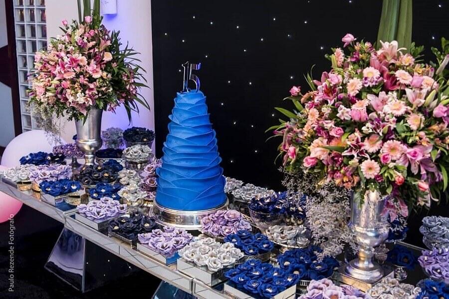 decoração festa de 15 anos com bolo azul e arranjo de flores