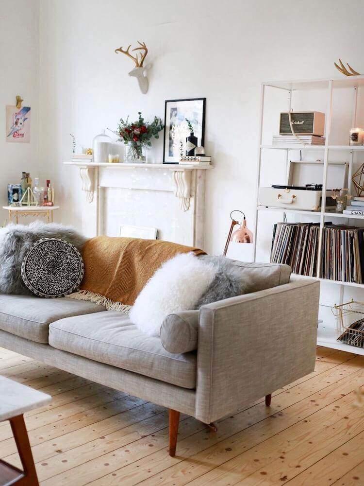 decoração hygge para sala com piso de madeira sofá cinza e manta decorativa Foto Deavita