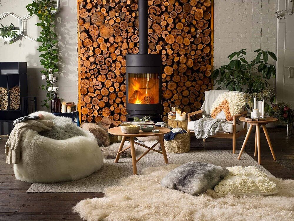 decoração hygge para sala de estar ampla com lareira e puff com tapete de pelos Foto Secret Roomz