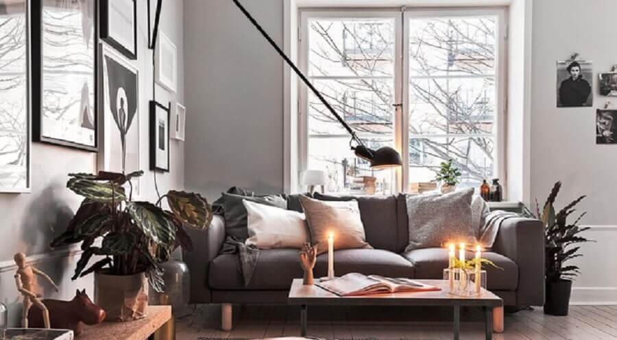 decoração hygge para sala de estar com luminária de parede e plantas Foto Ansa