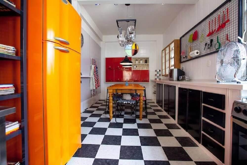 decoração para cozinha retrô com piso xadrez preto e branco e geladeira laranja