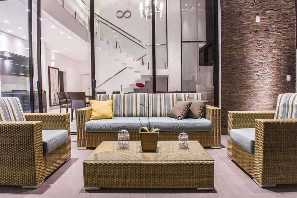 decoração para sala com móveis de vime almofadas listradas e parede revestida com pedras -Foto Haus Arquitetura
