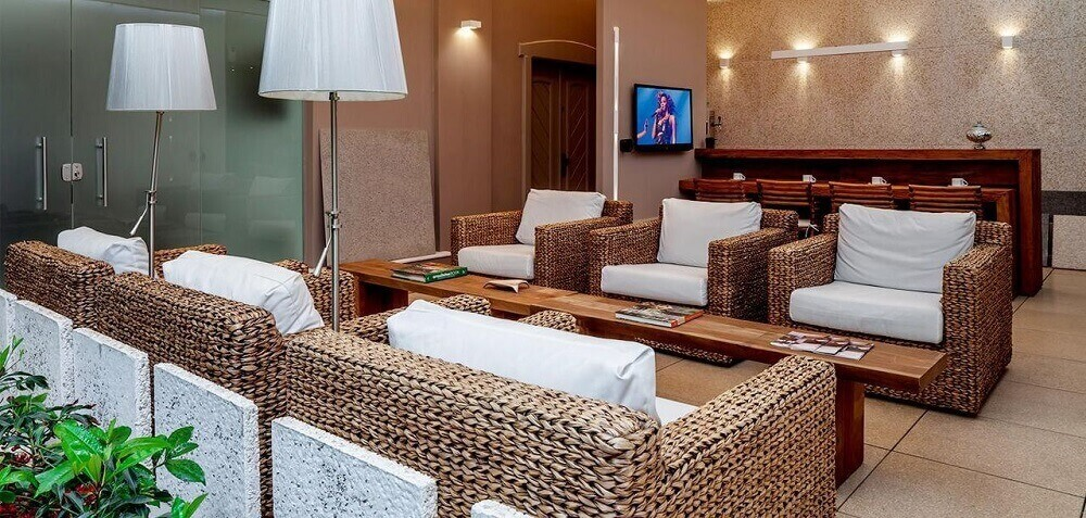 decoração para sala de espera com móveis de vime e pesa de centro de madeira Foto Fantin Siqueira arquitetos