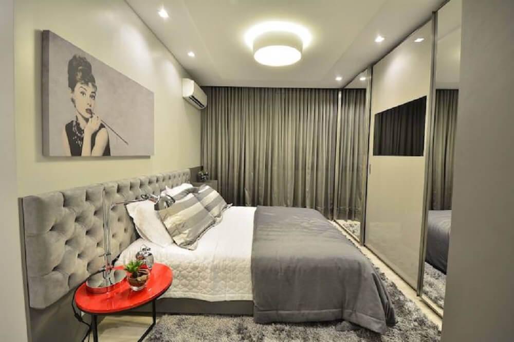 decoração quarto cinza com cabeceira queen capitonê e criado mudo vermelho