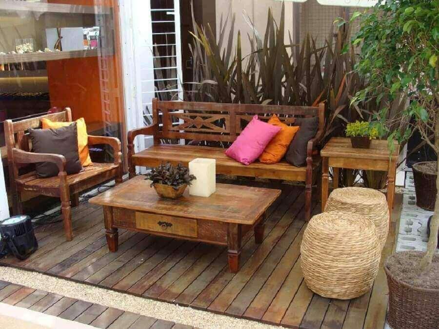 decoração rústica para varanda com móveis de madeira e puffs com fibras naturais