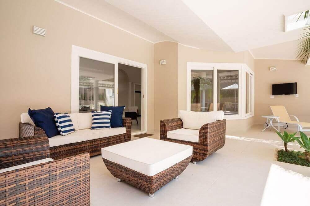 decoração sofisticada com móveis de vime para varanda com assento branco Foto Arquiteta Petini