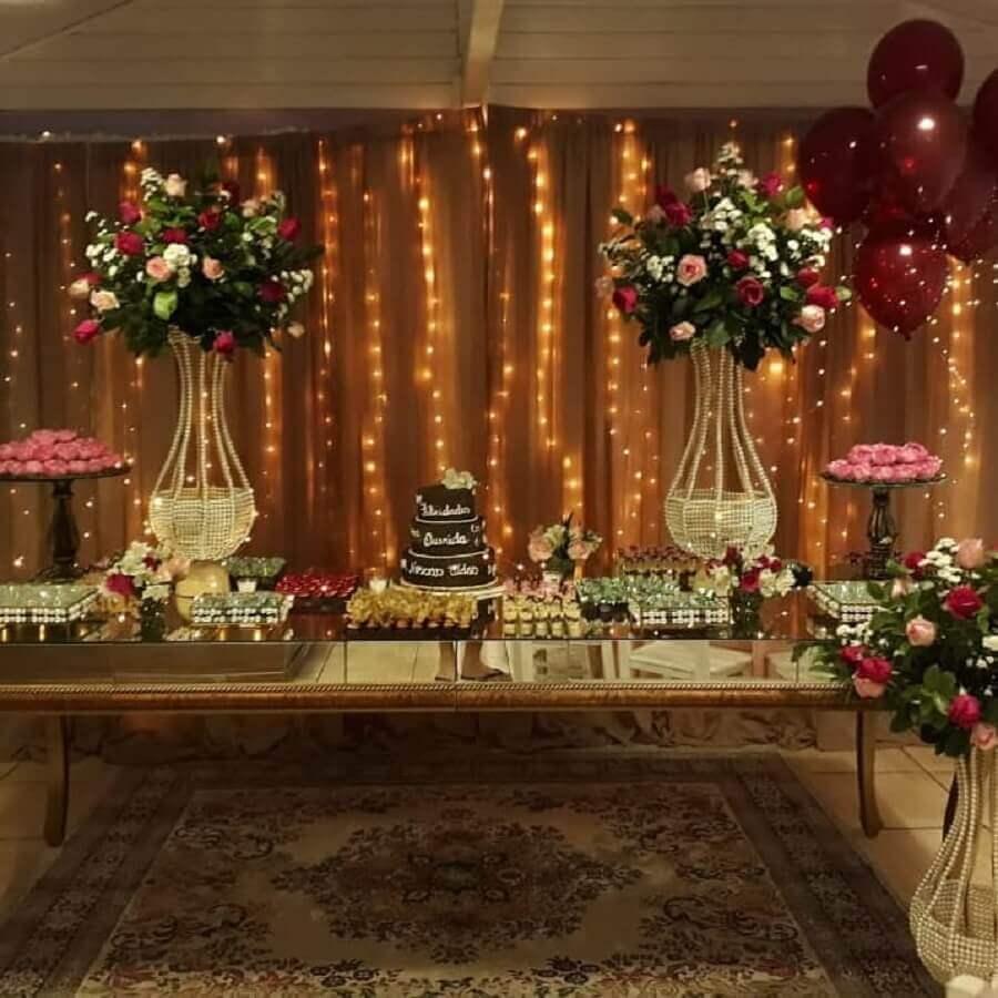 decoração sofisticada para festa de 15 anos com pisca pisca mesa espelhada e grande arranjo de flores