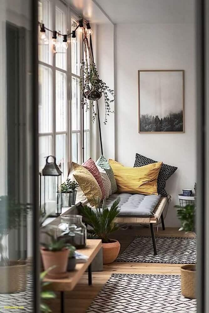 estilo hygge para decoração com varal de lâmpadas tapete com estampa geométrica e almofadas coloridas Foto Fontana