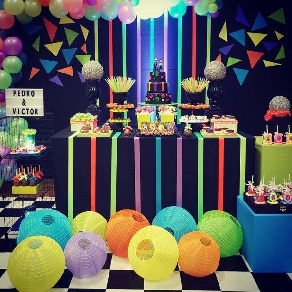 Invista em balões, fitas e acessórios coloridos para complementar a mesa do bolo.