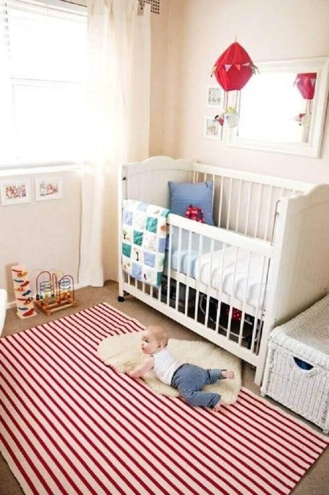 quarto de bebê decorado com tapete listrado vermelho e branco
