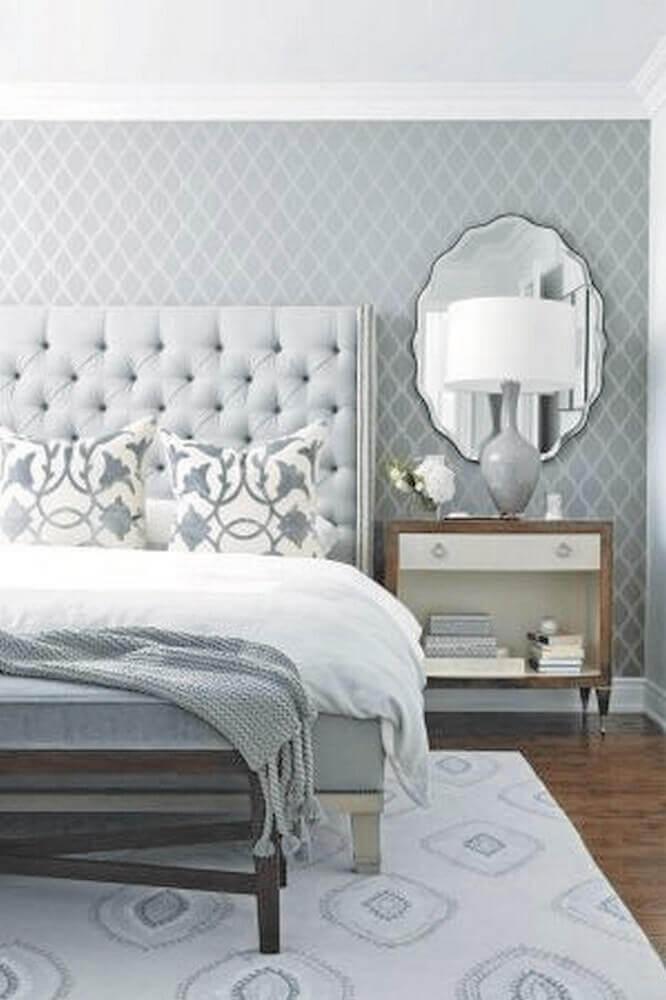 quarto de casal decorado em tons de cinza com papel de parede espelho e cabeceira capitonê- Foto Futurist Architecture