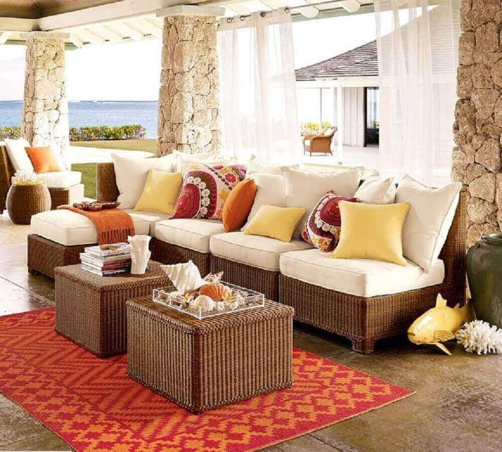 varanda decorada com móveis de vime e tapete estampado de vermelho e laranja Foto Dalworth Rug Cleaning