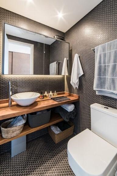 Banheiro com revestimento escuro e bacia com caixa acoplada branca Foto de Pietro Terlizzi