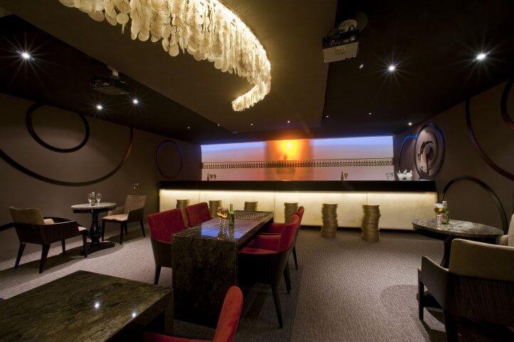 Bar com mesas com tampo de granito escuro Projeto de Samira Jarouche