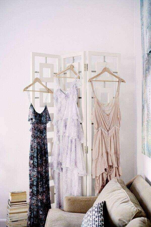 Biombo com vestidos pendurados