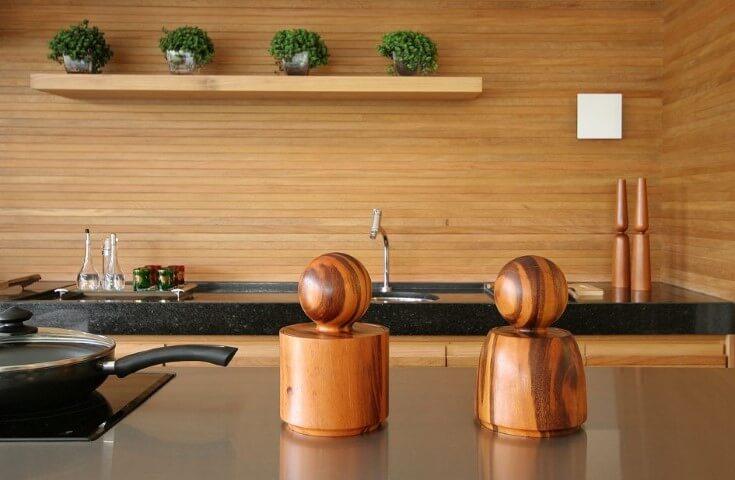 Cozinha gourmet revestida em madeira e bancada de granito preto Projeto de Sandra Picciotto