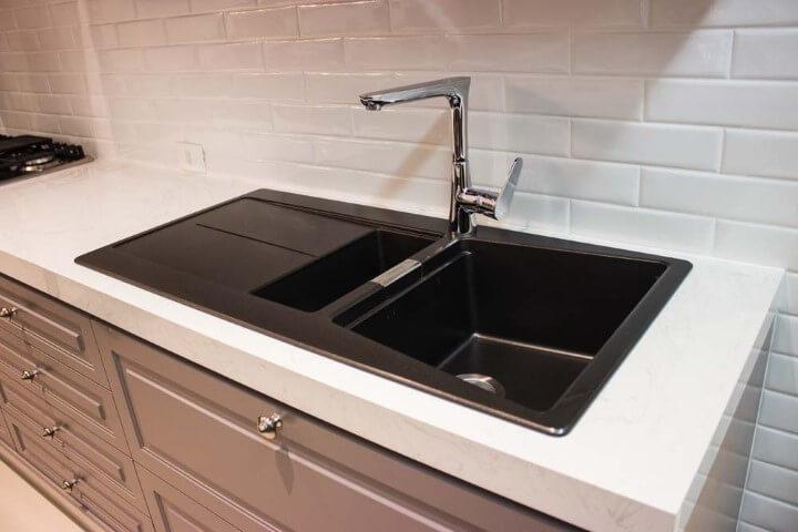 Cozinha planejada com bancada de granito branco e pia preta Projeto de Lojas Atua Prime