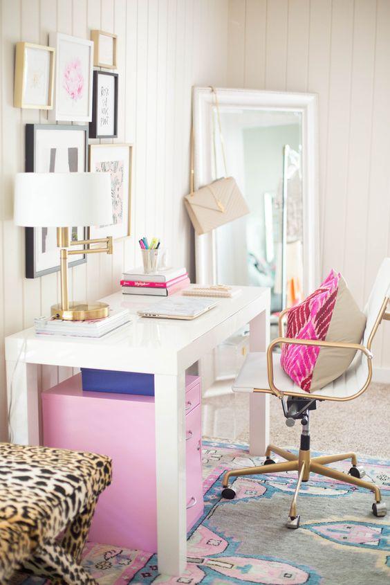 Escrivaninha branca com cadeira dourada e detalhes em rosa pink