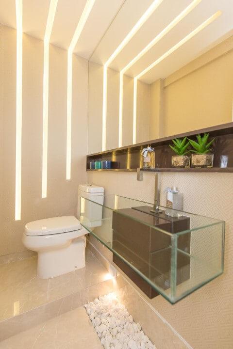 Lavabo com fendas iluminadas e bacia com caixa acoplada embaico Foto de Andrea Fonseca