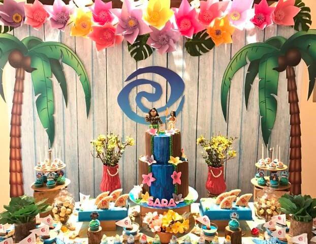 Mesa de festa Moana com bolo que imita cachoeira Foto de Catch My Party