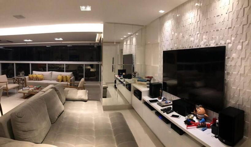Sala de estar com painel de espelhos e parede de gesso 3D Projeto de Ana Cinthia Lopes