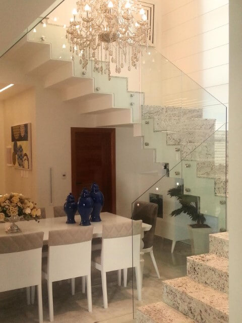 Sala de jantar sofisticada com escada de granito clara Projeto de Rafael Simonazzi
