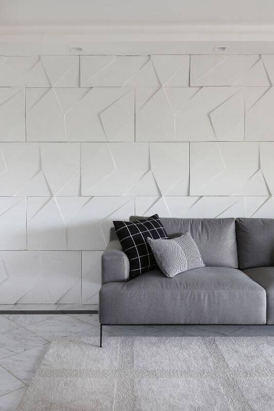 Sala moderna com parede com gesso 3D atrás do sofá cinza Projeto de Bianchi Lima