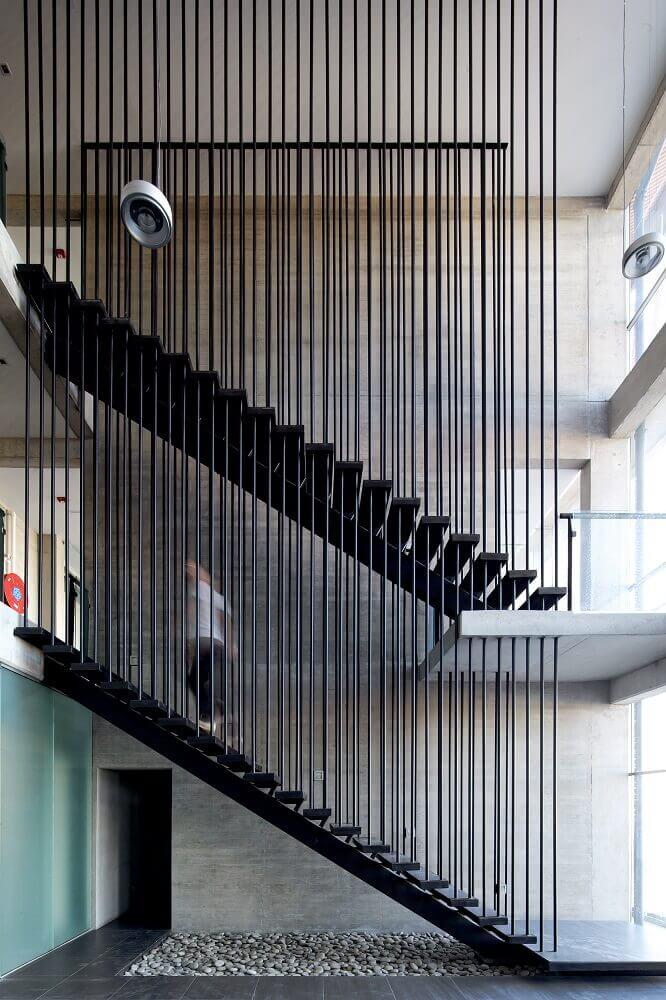 ambiente moderno com escada preta com guarda corpo com barras de ferro Foto ArchDaily (1)