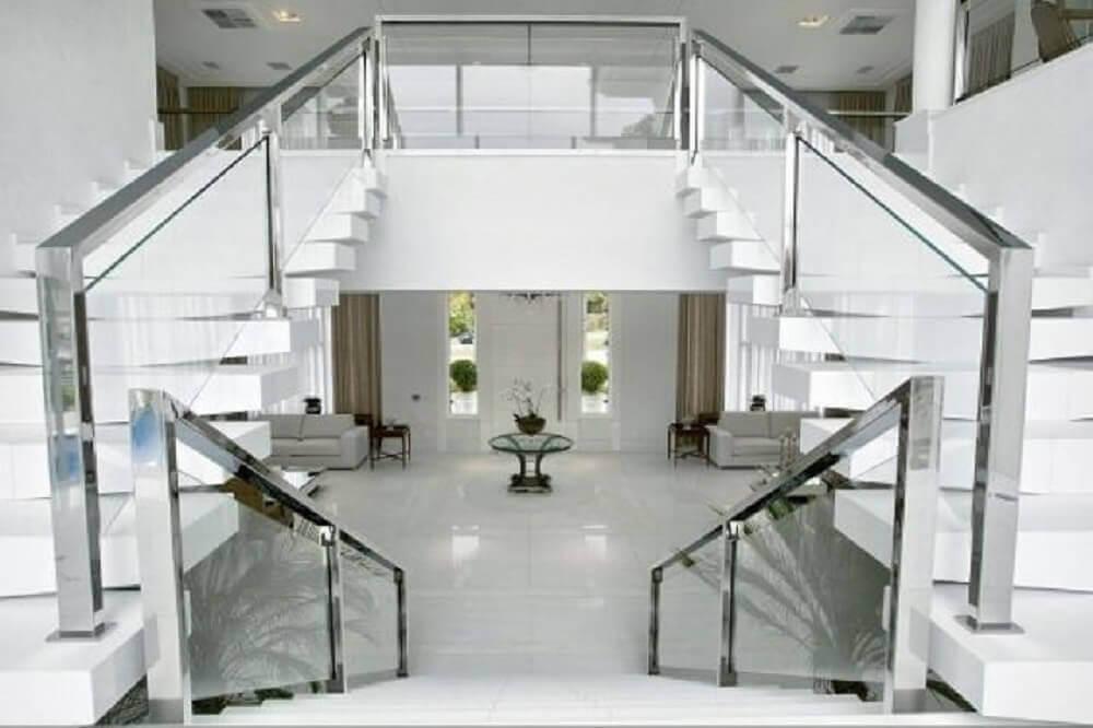 ambiente todo branco com guarda corpo de vidro e corrimão de alumínio Foto Bianka Mugnatto