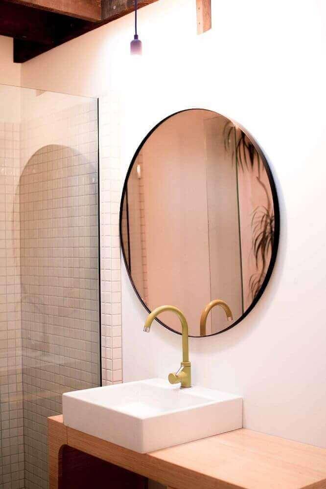 banheiro decorado com espelho bronze redondo e bancada de madeira Foto Ceramics tiles