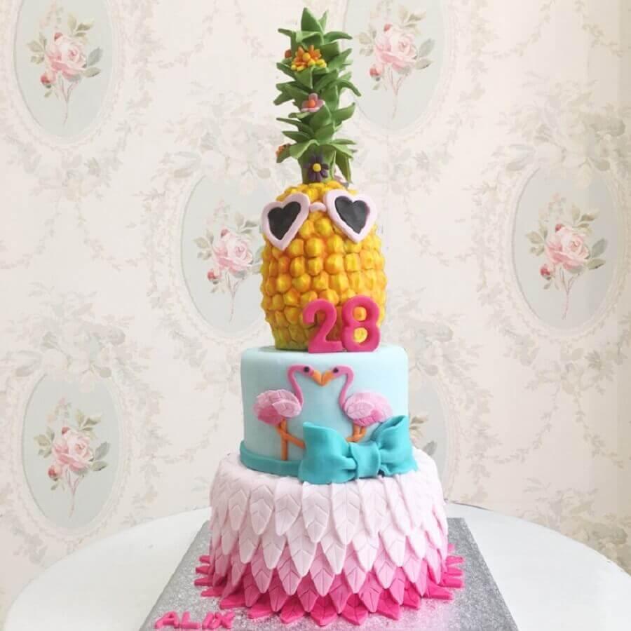 bolo tropical com flamingos e abacaxi no topo Foto Debogato