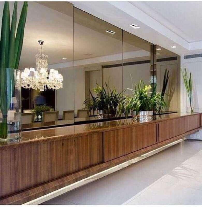 buffet de madeira decorado com vasos de plantas e parede revestida de espelho bronze Foto Pinterest