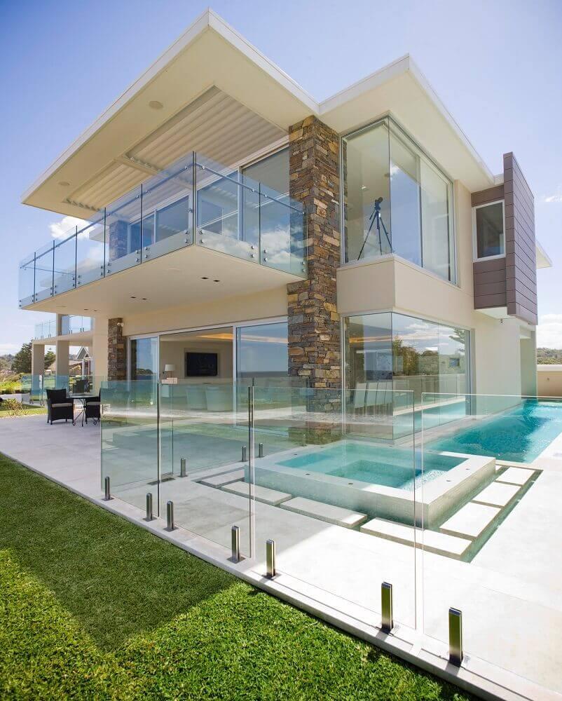 casa com guarda corpo de vidro por toda sacada e entorno da piscina Foto Architizer