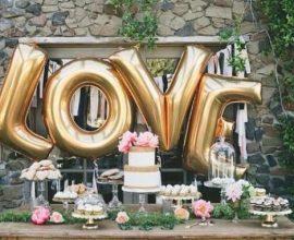 Balões metálicos na mesa do bolo transforma a decoração de noivado