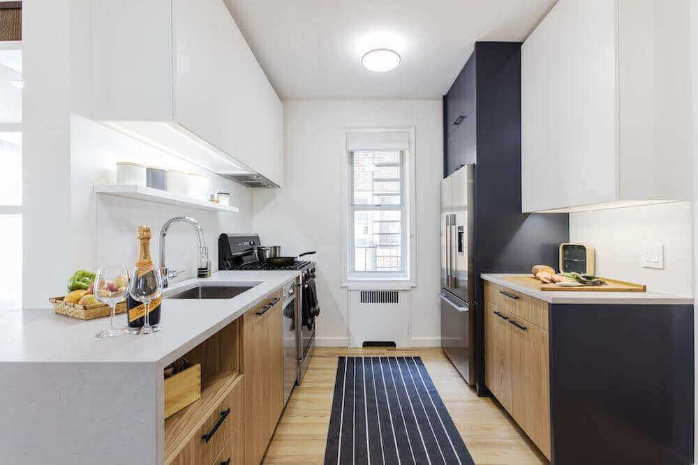 cozinha corredor planejada com piso de madeira e tapete listrado preto e branco Foto Pinterest