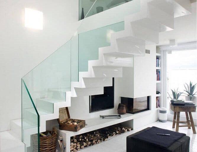 decoração clean e moderna com guarda corpo de vidro e lareira embaixo da escada  Foto Pinterest